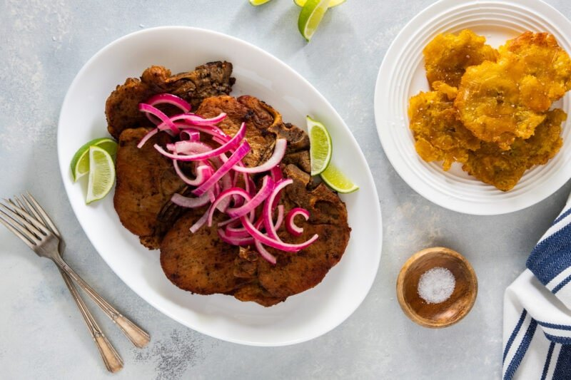 Fried pork chops on a white plate topped with red onions.
