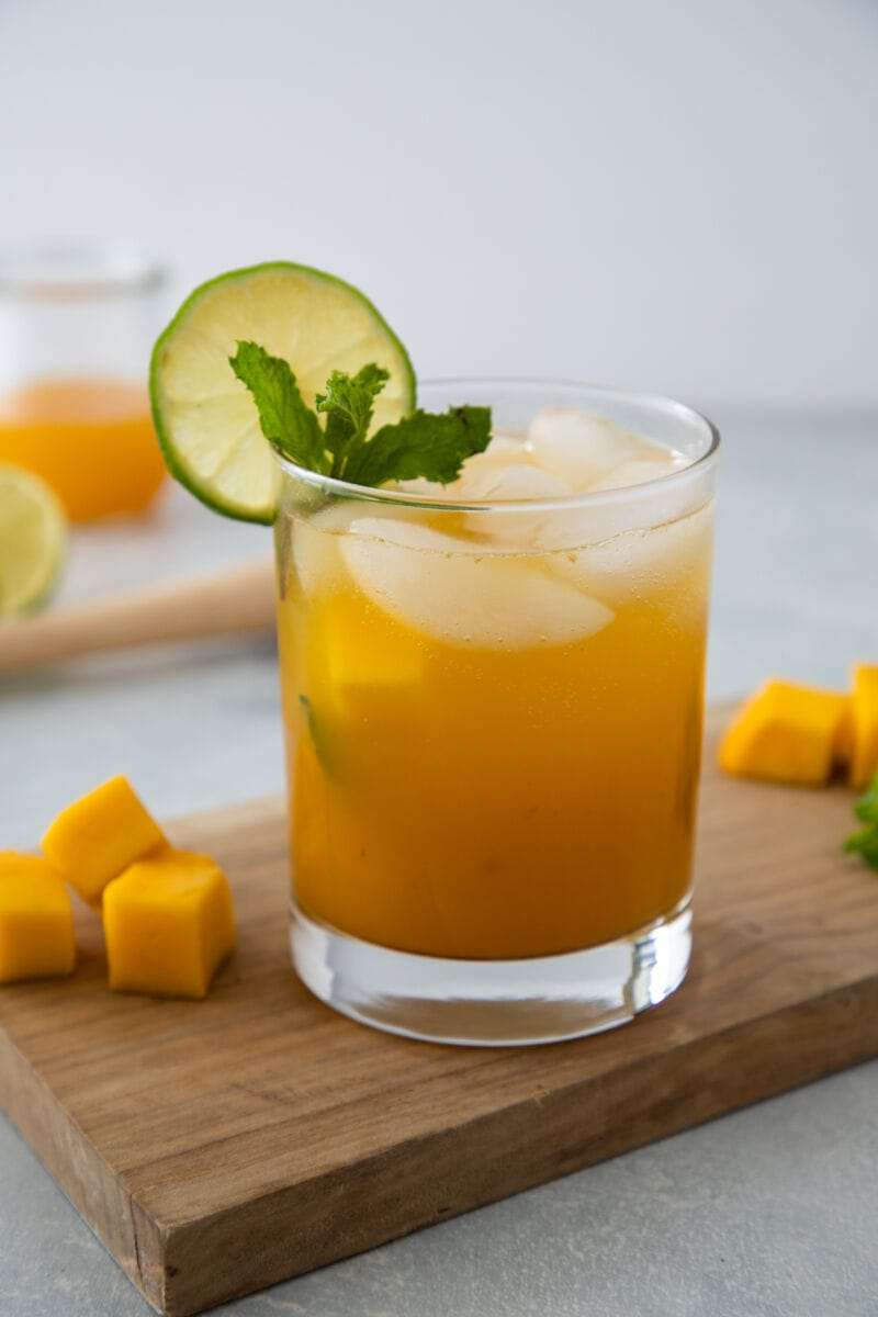Mango Mojito in a glass garnished with lime and mint
