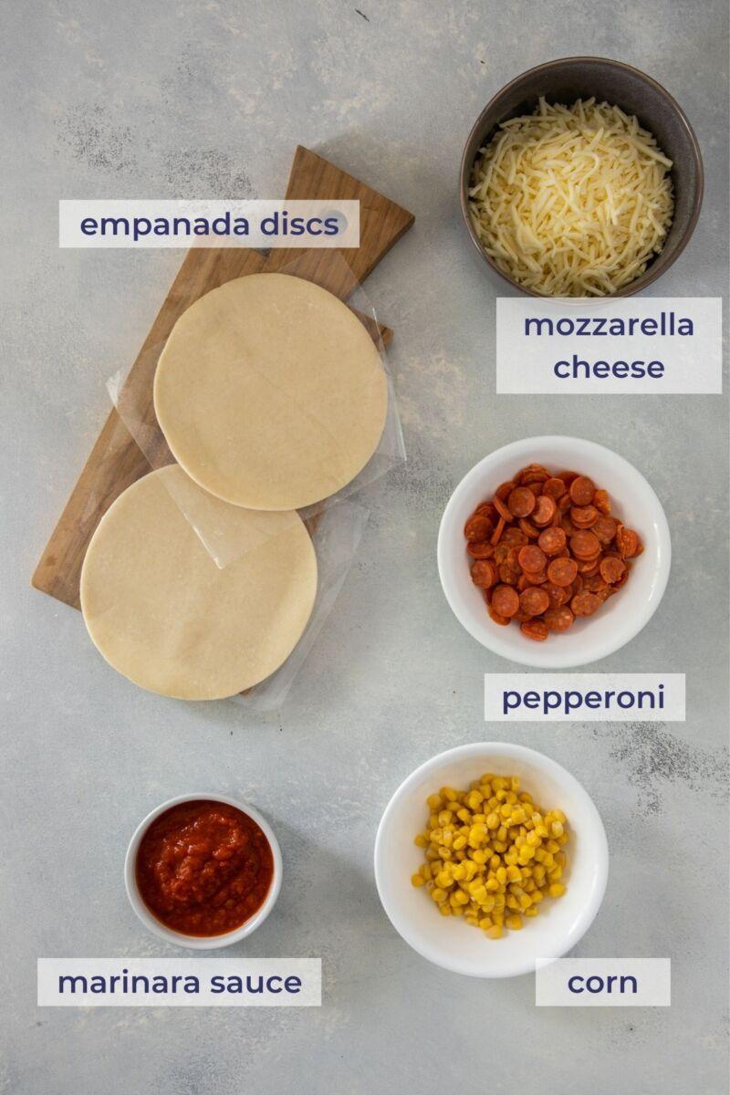 Pepperoni Pizza Empanadas ingredients on a board