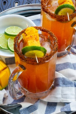 Mango Michelada served in a glass with mango and lime garnish.