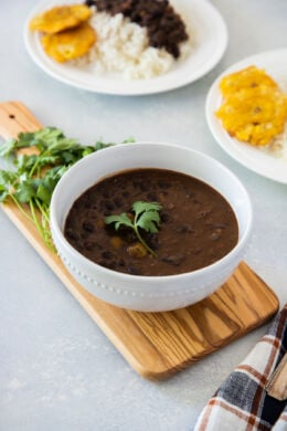 A white bowl with black bean stew garnished with fresh cilantro.