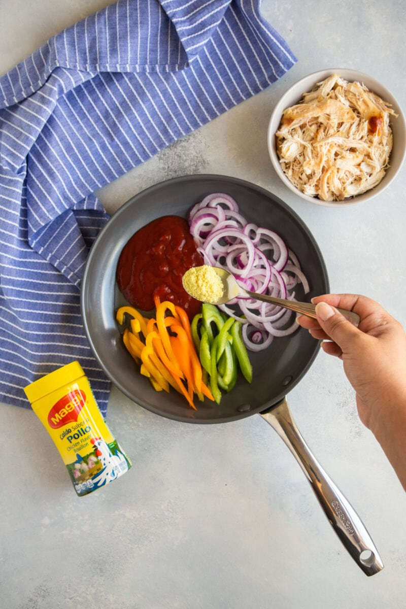 onions, bell peppers and tomato sauce in a pan