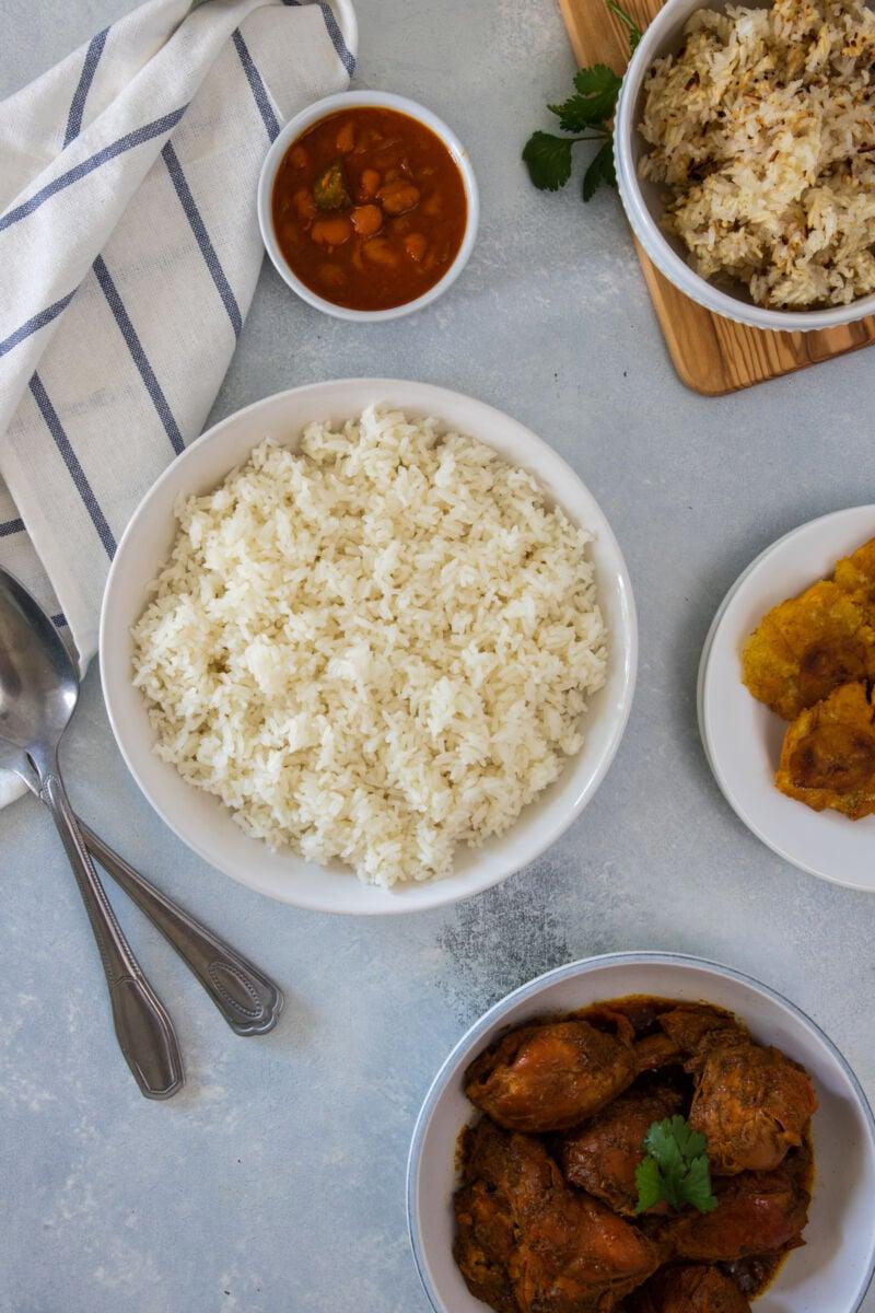 Fotografía superior de un plato de arroz blanco junto a frijoles y estofado de pollo.