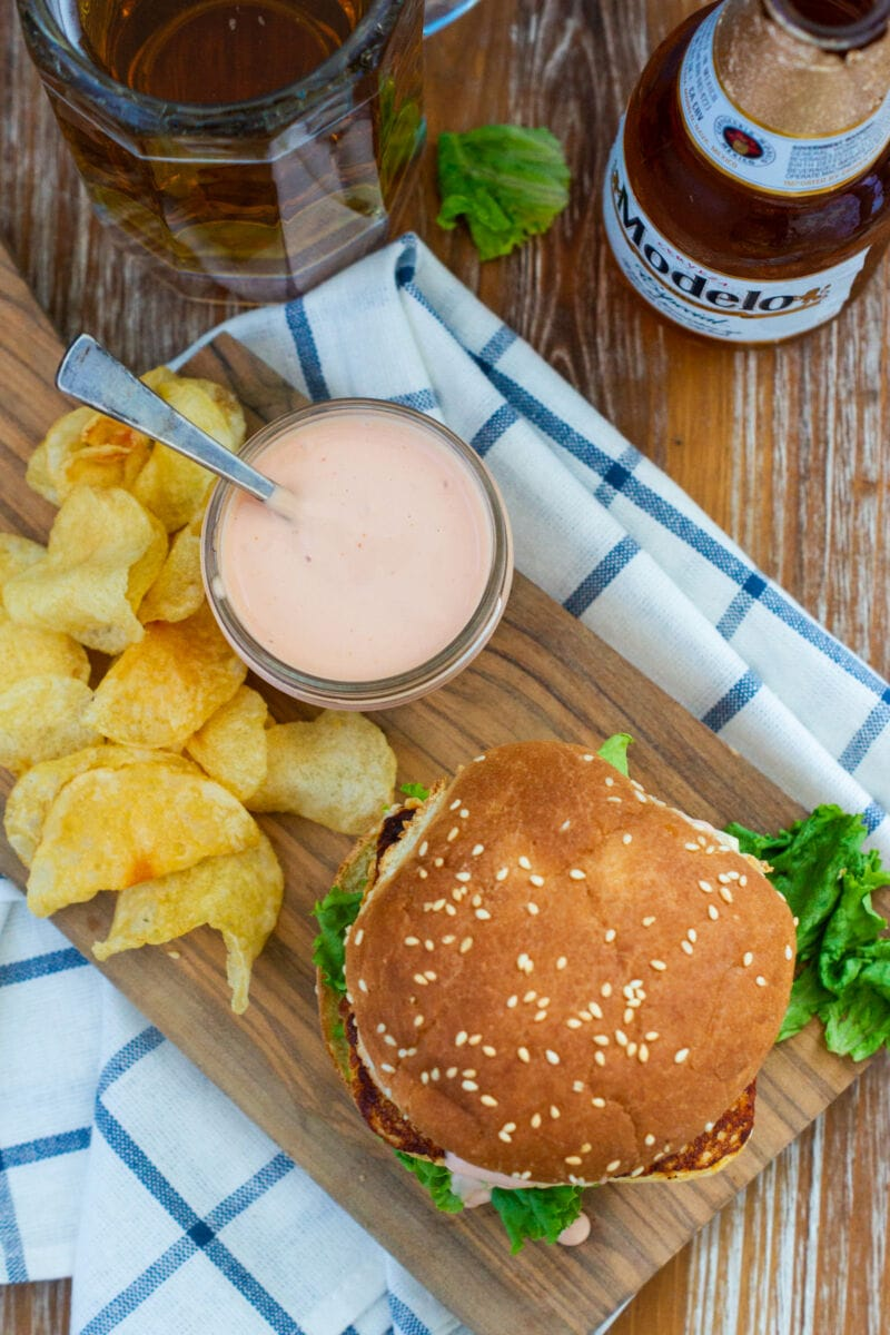 Overhead shot of a burger next to a jar of sauce and some chips.