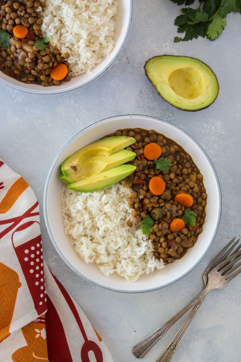 Lentil stew on a plate served with rice and avocado.