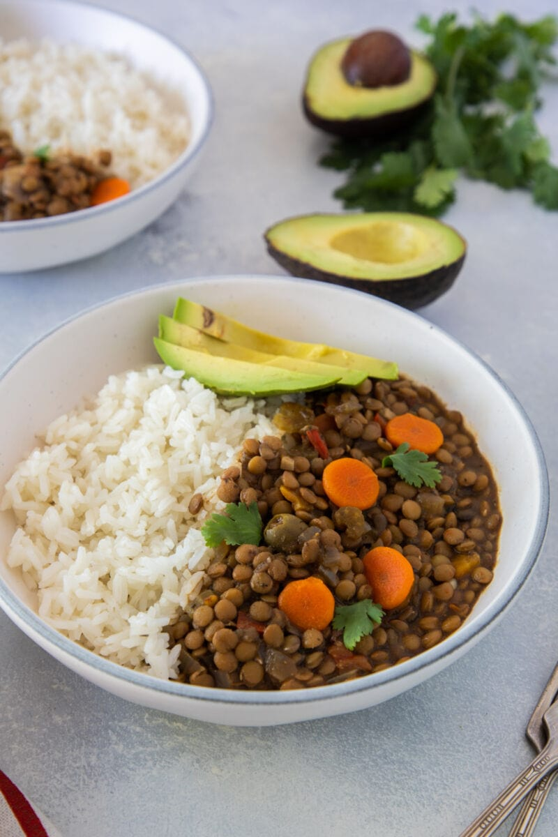 Lentil stew topped with sliced avocado and served with white rice.