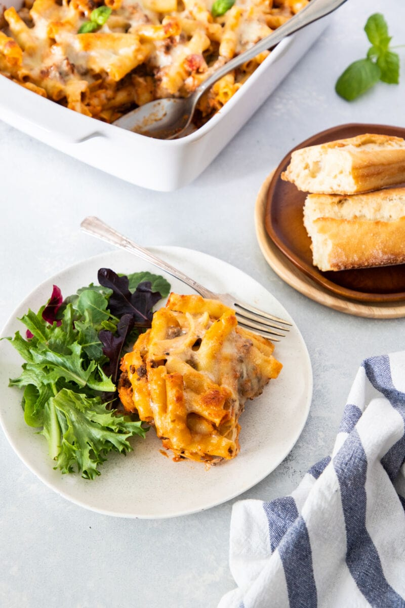 ricotta baked ziti served on a plate with salad and bread on the side
