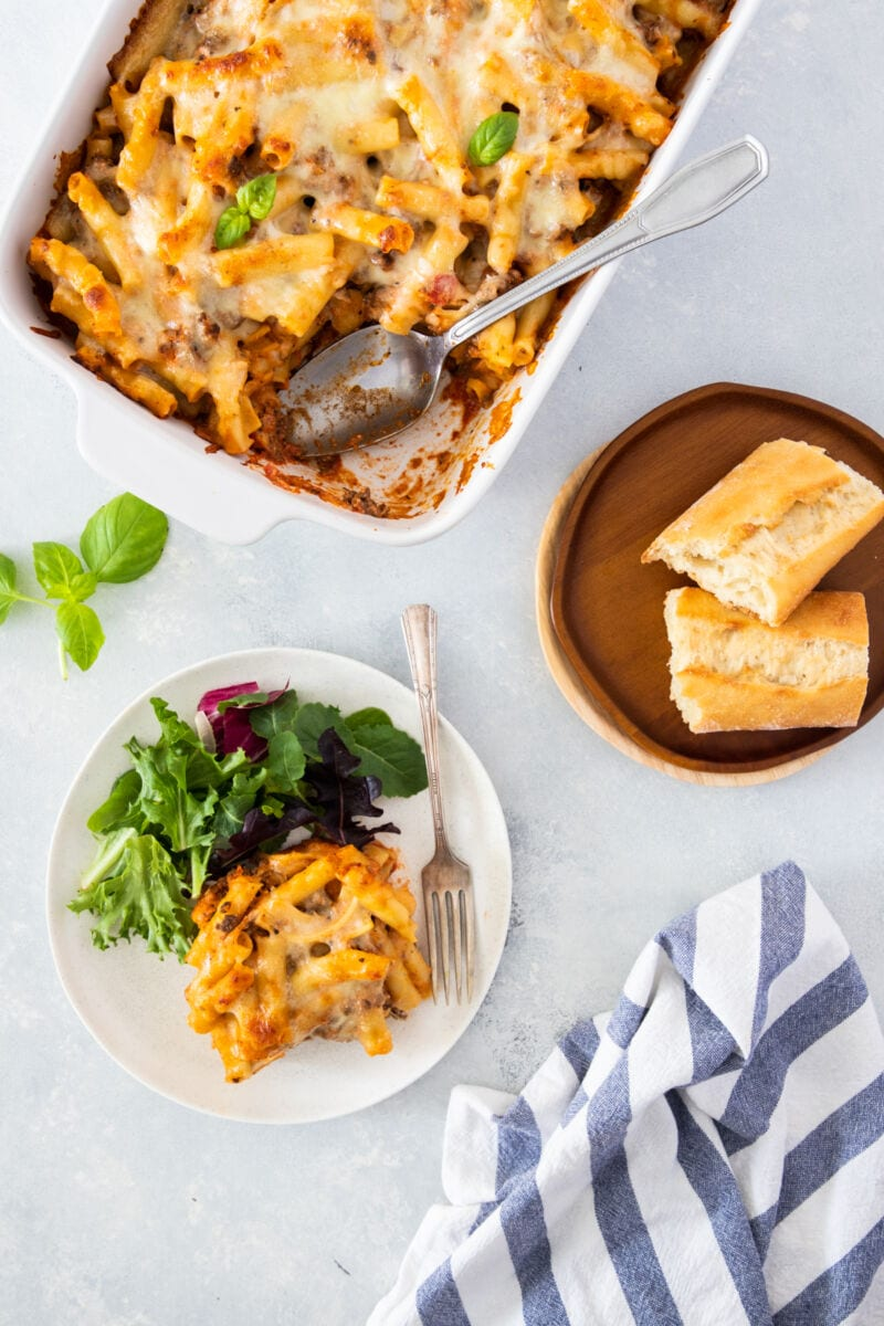 ricotta baked ziti served on a plate with salad on the side