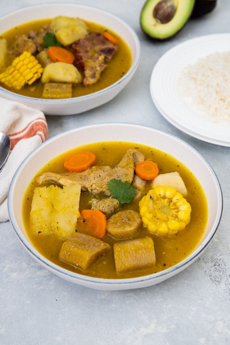 Sancocho served in a white bowl with white rice on the side