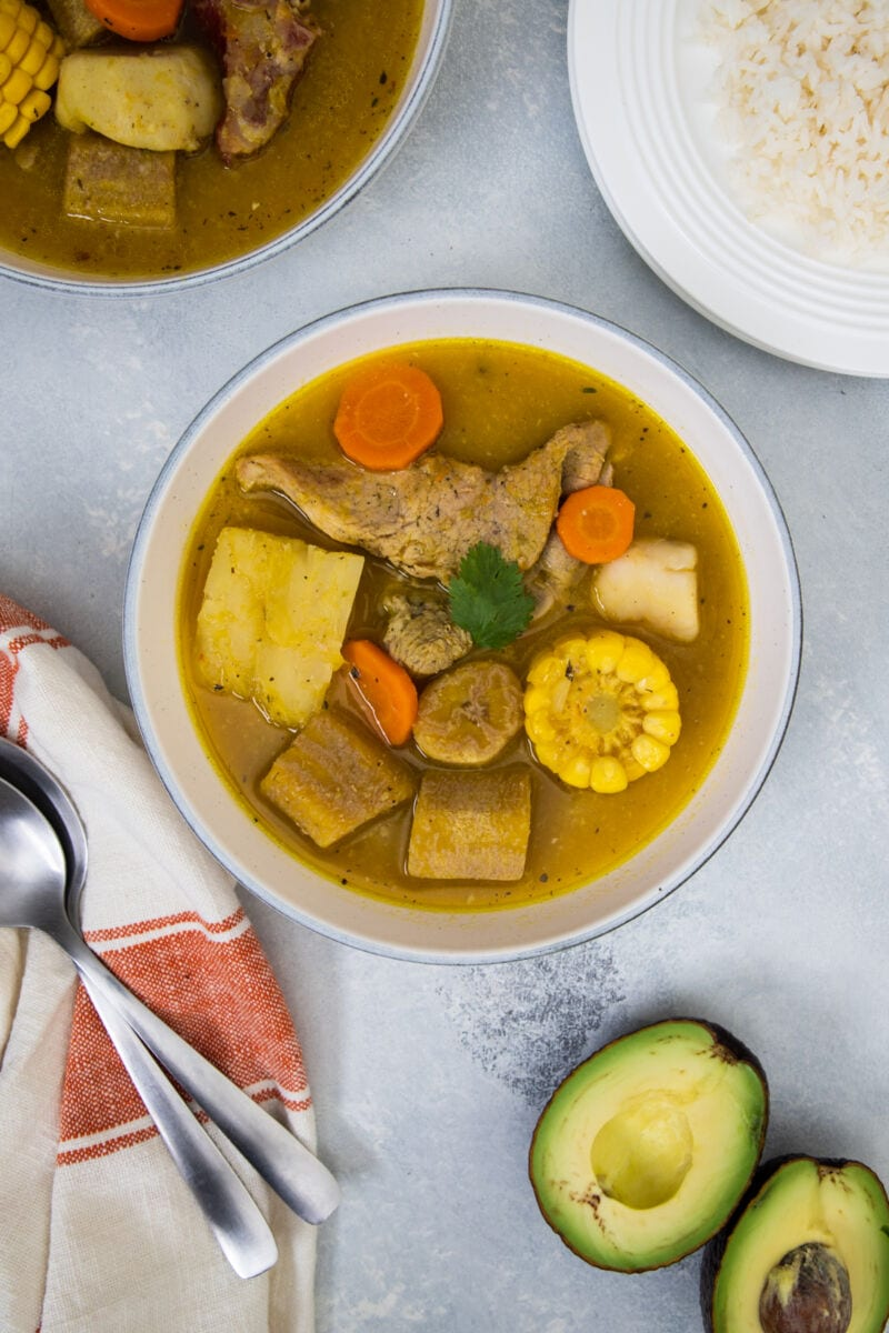 Sancocho served in a white bowl with rice and avocado on the side